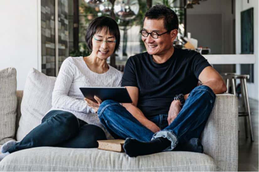 man and woman couple on couch using payment calculator